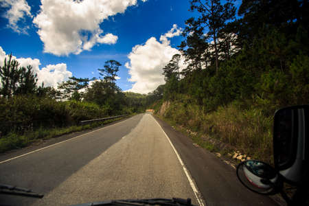 view of sunny highway among wooded hills against cloudy blue sky out of bus window
