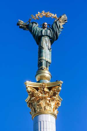 closeup bronze sculpture of Ukrainian girl with golden garland on column of Independence in Kiev against blue sky