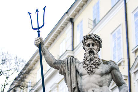 closeup city sculpture of Poseidon with three-pointed trident against building