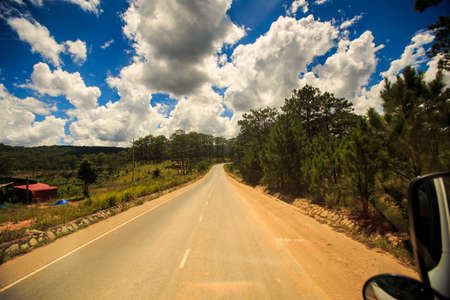 sunny highway vanishes into space among hilly country land against cloudy blue sky