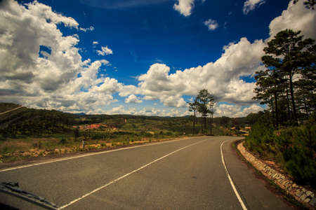 sunny highway bend against hilly wooded country land and blue cloudy sky Stock Photo