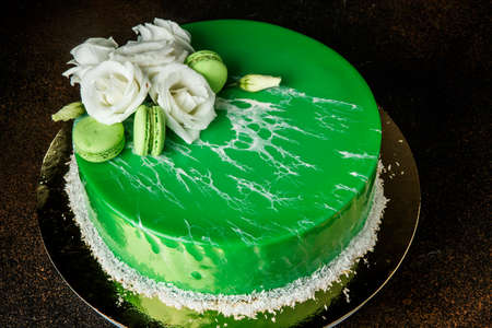glazed mousse green cake decorated with white roses and mint macaroons Foto de archivo