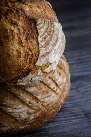 two delicious whole homemade round white wheat bread lie on  dark wooden table