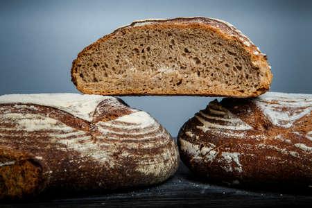 closeup whole and half pieces of  tasty handmade round black bread on gray background horizontal Фото со стока