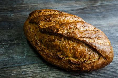 handmade oblong wheaten bread covered with honey lie on dark table background Imagens
