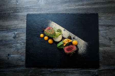 Top view on two pieces of roasted meat decorated with puree and sauce on black plate on wooden table in restaurant