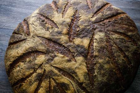 Macro  big whole handmade round black bread with interesting texture lie on dark wooden table Stock fotó