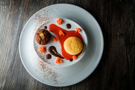 top view of delicious dessert of round small cake and chocolate truffle with red vanilla sauce decoration on white plate Imagens