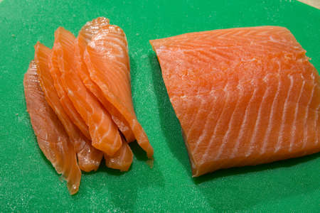 one big part of salmon fillet with  sliced pieces lies on green plastic tablet