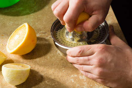 process of manual extraction of fresh lemon juice with squeezer Stockfoto