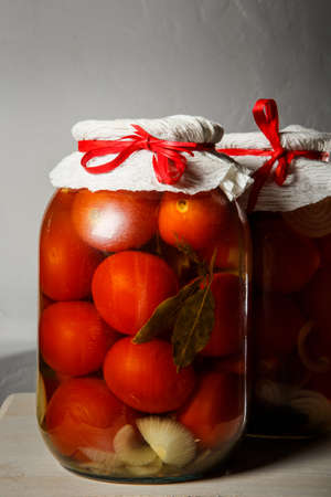closeup two big glass jars with homemade canned tomatoes stand on kitchen table against gray wall background 版權商用圖片