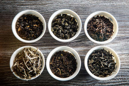 top view of different kinds of tea leaves in six white small round vessels on wooden table background