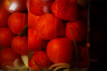 macro glass jar with homemade canned tomatoes stand on kitchen table against two other glass jars Stock Photo