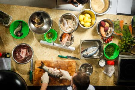 Vista dall'alto di filetti di pesce, limoni, carote e barbabietole, aneto e sale giacciono in ciotole sul tavolo da cucina beige