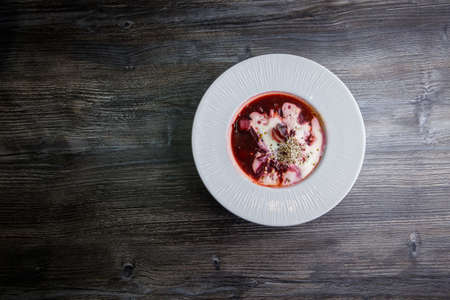 top view tasty ukrainian borscht decorated with sour cream and wheat sprouts served in white restaurant profound bowl