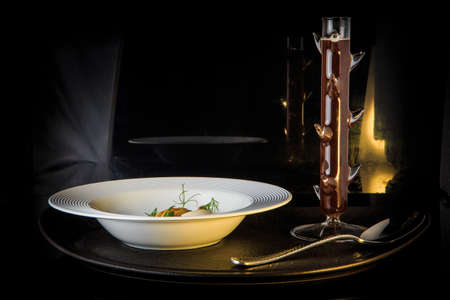 vegetarian soup with mushrooms, mozzarella cheese, and dill served in restaurant white plate and spoon on black background