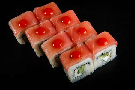 top view on roll sushi with tuna, cucumber, and cream cheese decorated with red sauce served on black background 스톡 콘텐츠