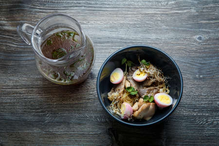 top view closeup noodles with shiitake mushrooms, chicken eggs and wheat sprouts served in deep black restaurant bowl and pitcher with broth on wooden table Imagens