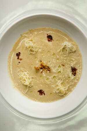 top view closeup beige seafood cream soup decorated with dried squid