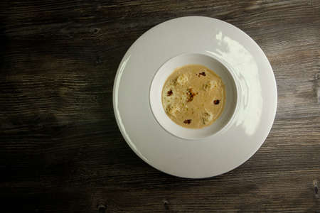 top view fresh seafood cream soup decorated with dried squid and soy sauce