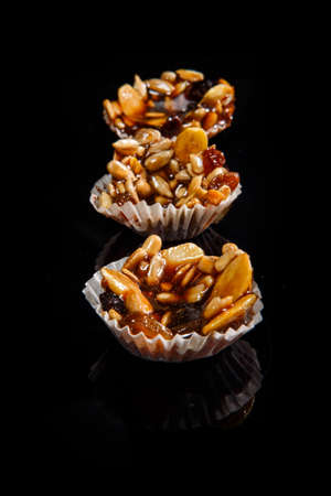 row of three of healthy useful handmade candies decorated with caramelized sunflower and pumpkin seeds on black mirror background Stok Fotoğraf - 121159069