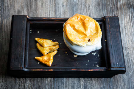 delicious white soup pot with bread on the top and three puff pastry cakes triangles served n black wooden tray