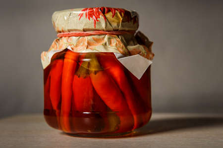 pickled red chili peppers in glass jar stand on table and gray background behind