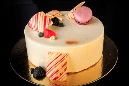 delicious round cake with white glaze decorated with purple macaron, colored chocolate and marmalade served on black background