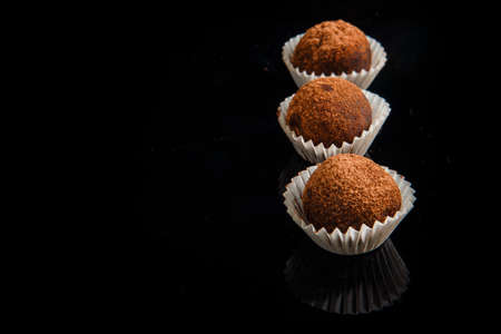 closeup row of three healthy useful organic handmade round chocolate candies decorated with brown cocao powder on black mirror background Stok Fotoğraf - 121159350