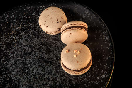 closeup three peanut macarons with chocolate served on black textured plate on black background