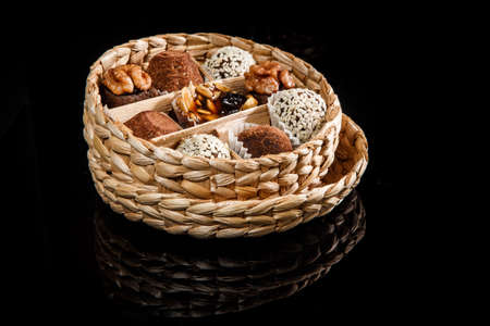 small handmade box filled with assorted healthy useful handmade candies decorated with caramelized sunflower and pumpkin seeds, cocoa powder, walnut and sesame seeds on black mirror background