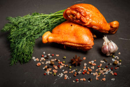 two smoked chicken thighs decorated with fresh green dill, garlic and spices served on black background Stock Photo