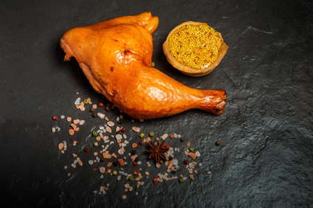top view of smoked chicken leg with spices and fresh mustard in grain served on black background