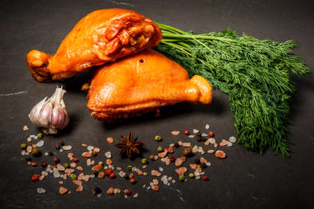 two smoked chicken thighs decorated with fresh green dill, garlic and spices served on black background Banque d'images