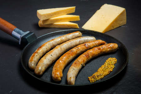 large frying pan with fried thin meat sausages and granular mustard served with sliced hard cheese on black background 写真素材