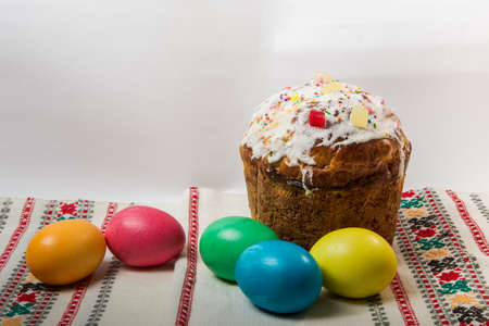Decorated Easter bread and colorful dyed Easter eggs served on a traditional Ukrainian embroidered towel