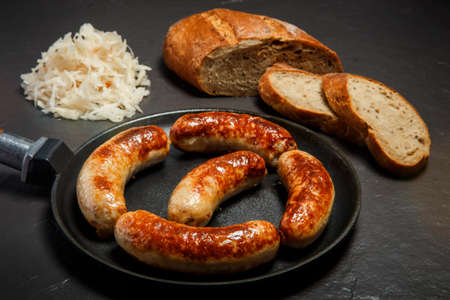 Five appetizing ruddy juicy sausages fried in large frying pan served with sliced rye bread and homemade sauerkraut on black background Standard-Bild