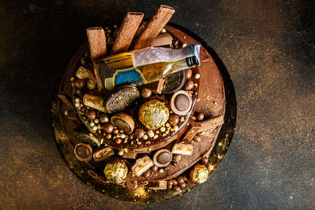 Top view of delicious two layers chocolate cake decorated with candies and cookies and sprinkled with food gold