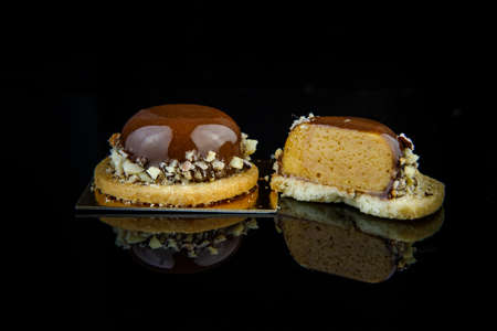 Sliced on half and whole french mini mousse pastry dessert covered with chocolate glaze and crushed nuts on black background Imagens