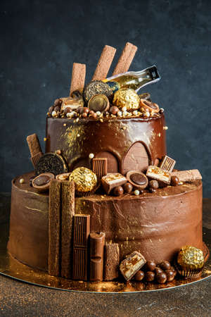 Fabulous chocolate cake decorated with candies and cookies and sprinkled with food gold