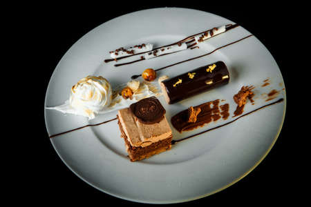 Top view of chocolate and caramel creamy mousse dessert on white restaurant plate on black background 版權商用圖片