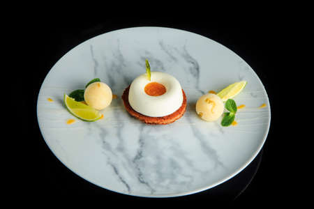 Top view single shortbread cookie with white mousse cream served with two spheres of ice cream and sliced limes 版權商用圖片