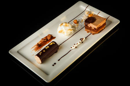 Top view on delicious chocolate and cream mousse dessert served on rectangle restaurant plate on black background