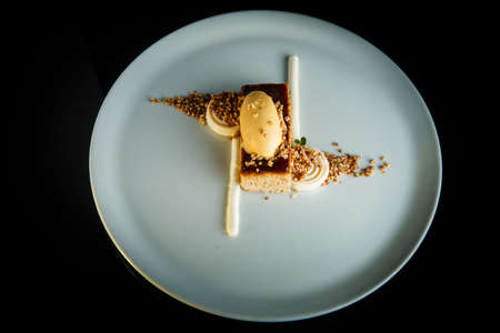 Top view on gluten-free baked dessert with ice cream and white mousse served against black background
