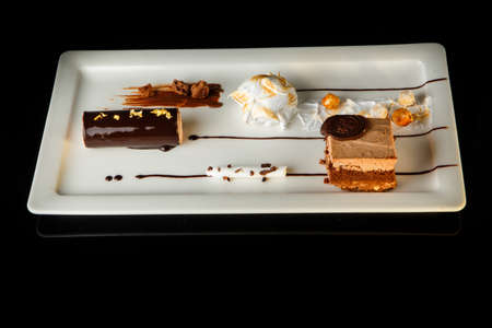 Delicious chocolate and white cream mousse dessert served on rectangle restaurant plate on black background