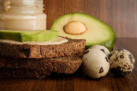 Closeup sliced avocado on rye bread slices, three quail eggs and tahini butter in glass jar on wooden background Imagens