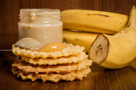 Closeup spoon with tahini butter and honey on top of Belgian waffles next to yellow bananas on wooden background Imagens