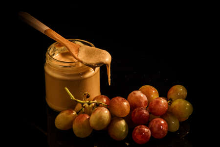 Small glass jar with creamy peanut butter with wooden spoon on top next to purple grapes served on black background