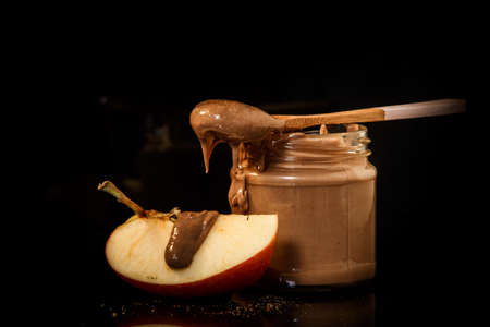 Closeup chocolate peanut butter in small glass jar with wooden spoon on top served with slice of apple Imagens