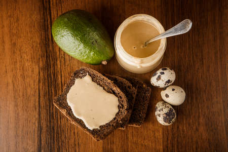 Top view on tahini butter in glass jar, sliced rye bread, whole avocado, and three quail eggs on wooden background